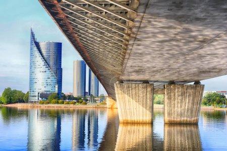View under Vansu bridge in Riga, Latvia. Modern building (left) and pillars of the bridge (right)