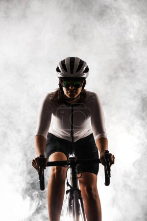Photo for Female roadbiker riding a bicycle against fog background - Royalty Free Image