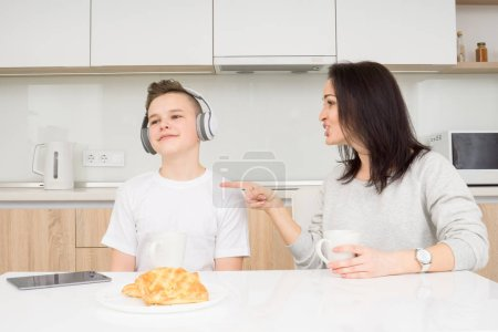 Photo for Mother scolds her son while he listening music and doesn't listen. Copcept of family conflict - Royalty Free Image