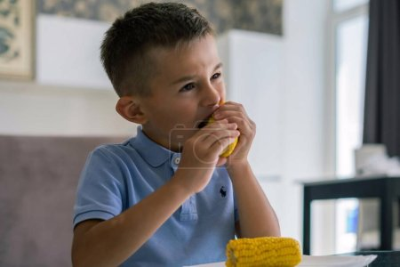 Photo for Kid eating cort at home. Boy bite boiled corn in living room - Royalty Free Image