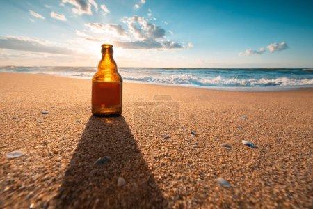 Foto de Hermoso amanecer de mar y botella de cerveza en la arena de la playa . - Imagen libre de derechos