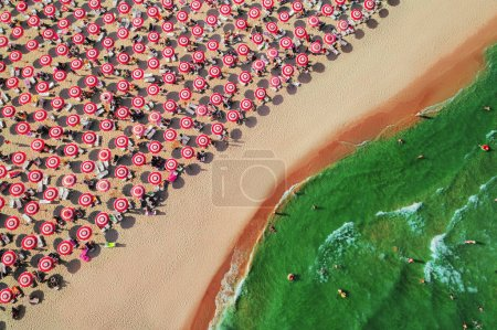 Aerial top view on the beach. Umbrellas, people, sand and sea waves