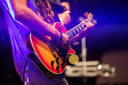 Photo pour Guitariste jouant sur une guitare basse électrique sur scène. Coloré, soft focus et flou fond. - image libre de droit