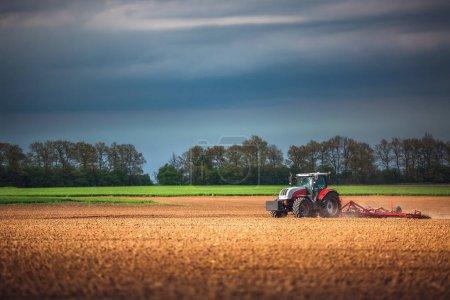 Foto de Agricultor en tractor preparación de tierra con cultivador de cama de siembra - Imagen libre de derechos