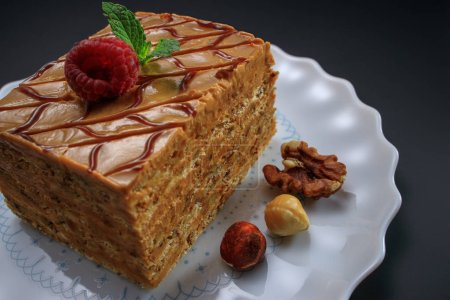 Photo for Cake piece with nuts, chocolate, biscuits and caramel cream isolated on black background. - Royalty Free Image