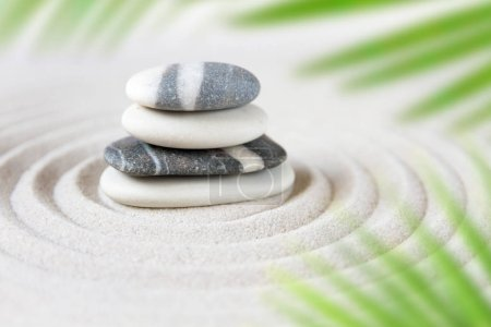 Photo pour Des pierres s'empilent dans le sable derrière les feuilles de palmier. Jardin japonais zen - image libre de droit