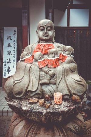 Photo pour Statue de Jizo avec bavoirs rouges dans le temple d'Arashiyama, Kyoto, Japon - image libre de droit