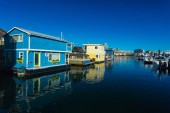 Colorful wooden floating houses on sunny summer day with blue sky.