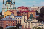 Kiev city. Old town. Ukraine. Beautiful view of the ancient street Andrew's Descent and the St. Andrew's Church among green trees of the Castle Hill in Kyiv