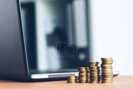 Photo pour Empilés les colonnes des pièces en argent et ordinateur portable dus à l'arrière-plan des finances, économie et notion de budgétisation - image libre de droit