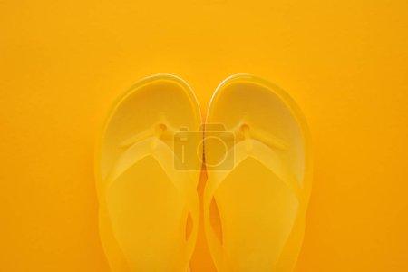 Photo for Top view of yellow flip flops pair on same color background with copy space. Beach sandals or slippers in minimalistic warm summer toned composition. - Royalty Free Image