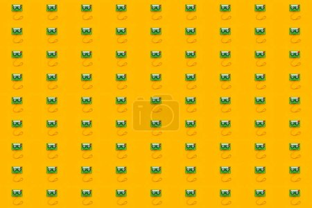 Seamless pattern background of audio cassettes with tangled tape on bright yellow backdrop, minimalistic top view composition