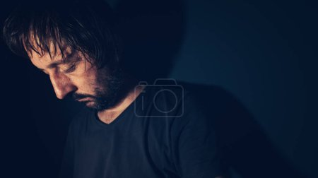 Photo for Mental health and depression concept, sad depressed man sulking in dark interior - Royalty Free Image