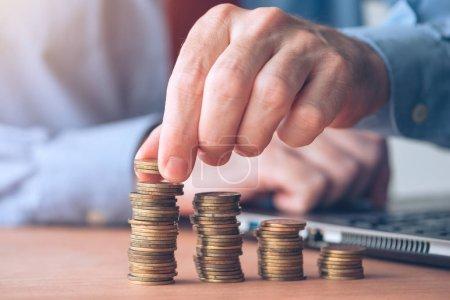 Photo pour Empileur de pièces, homme d'affaires avec de l'argent empilé dans le bureau faire la comptabilité, la budgétisation et les calculs fiscaux - image libre de droit