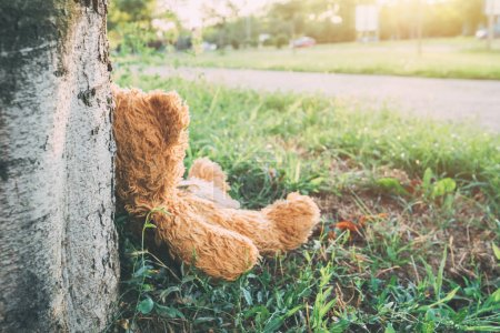 Photo for Miserable abandoned teddy bear outdoors leaning on to tree - Royalty Free Image