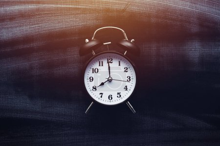 Photo for It is school time, alarm clock on blackboard - Royalty Free Image
