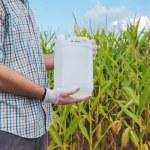 Farmer holding pesticide chemical jug in cornfield...