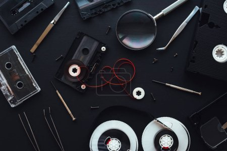 Flat lay audio and video cassette parts on dark background, top view of retro technology and media concept