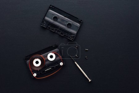Flat lay audio cassette parts on dark background, top view of retro technology and media concept