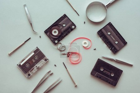Flat lay audio cassette parts on pastel blue background, top view of retro technology and media concept