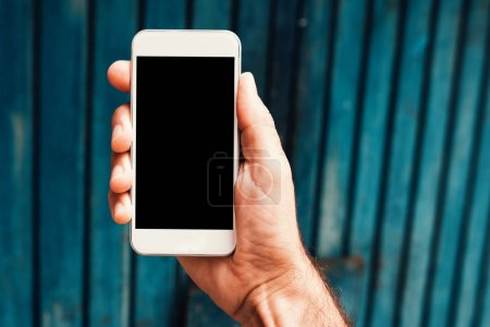 Photo for Hand with smartphone mock up screen in urban surrounding. Man holding mobile phone device with blank display. - Royalty Free Image