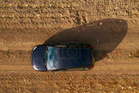 Photo pour Vue aérienne de la voiture noire sur chemin de terre à travers la campagne, vue de dessus de véhicule tout terrain à moteur de drone pov - image libre de droit