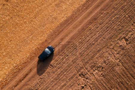 Photo for Aerial view of black car on dirt road through countryside, top view driving vehicle from drone pov - Royalty Free Image