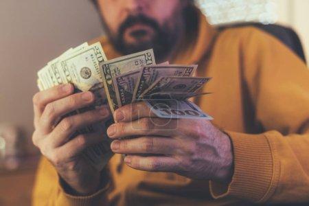Foto de Hombre casual es contar billetes de dólar estadounidenses, cerca de las manos con dinero - Imagen libre de derechos