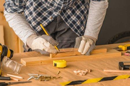 Carpenter marking pine wood plank for cutting