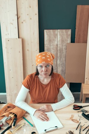 Photo for Portrait of self employed female carpenter wearing bandanna sitting at the desk in her woodwork workshop surrounded by various tools of trade - Royalty Free Image