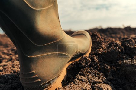 Photo for Farmer in wellington rubber boots making first step in field, close up. Beginning of agricultural season and starting of activities on farmland. - Royalty Free Image