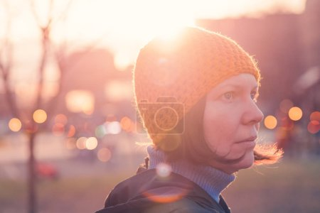 Photo for Portrait of beautiful woman in 40s against autumn sunlight in the park, female person wearing yellow cap looking into distance - Royalty Free Image