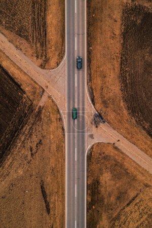 Photo pour Deux voitures sur une route droite à travers la campagne en automne après-midi vue aérienne de drone pov - image libre de droit