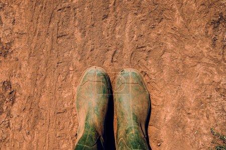 Photo pour Fermier en bottes en caoutchouc debout sur un chemin de terre, vue de dessus - image libre de droit
