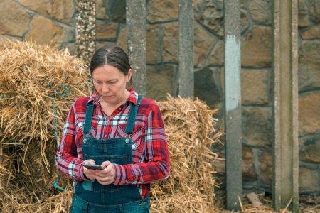 Photo pour Agricultrice dactylographiant sms message sur téléphone portable devant la meule de foin de la ferme - image libre de droit