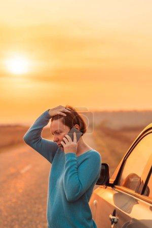 Photo pour Femme appelant sur téléphone portable pour de l'aide et de l'aide sur la route après que sa voiture est tombée en panne au coucher du soleil d'automne sur la route à travers la campagne, accent sélectif - image libre de droit