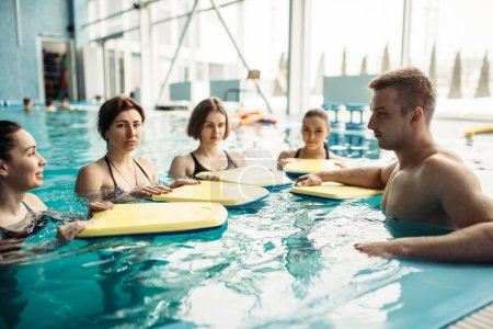 aqua aerobics workout with equipment in water sport center, indoor swimming pool, recreational leisure