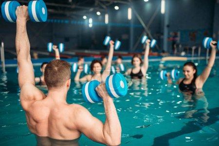 Foto de Entrenamiento de aqua aerobics con pesas en el centro de deportes de agua, piscina, ocio recreativo - Imagen libre de derechos
