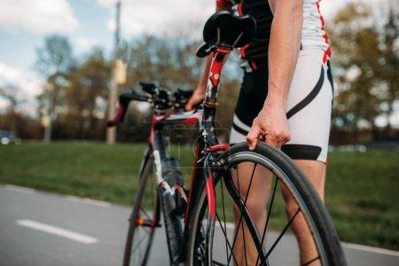 Photo pour Cycliste masculin dans le casque et vêtements de sport permet de régler la moto avant la compétition. Séance d'entraînement sur la piste cyclable, course cyclotourisme - image libre de droit