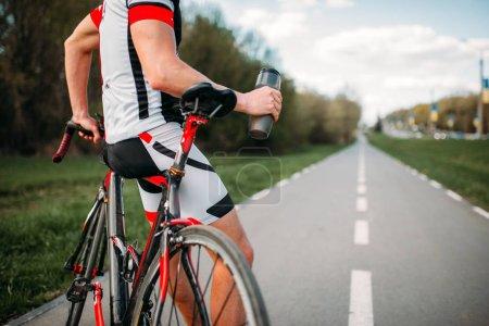 Photo pour Bycyclist dans le casque et vêtements de sport sur l'entrainement de vélo. Cyclisme sur piste cyclable, formation sur route asphaltée - image libre de droit