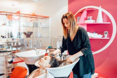 Photo pour Coiffeur lave les cheveux du client dans le salon de coiffure. Soins capillaires professionnels en studio de beauté, cliente et esthéticienne - image libre de droit