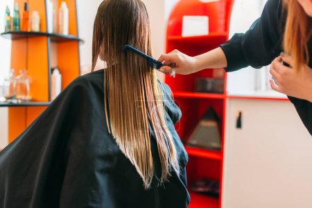 Hairdresser runs the comb, female client in hairdressing salon. Hairstyle making in beauty studio