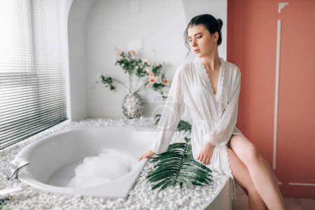 slim woman in white bathrobe sitting in bath with foam, bathroom interior
