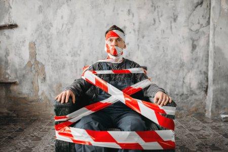 Photo pour Homme enveloppé dans du ruban de la scène du crime et assis dans le fauteuil dans la chambre de grunge. Personne de sexe masculin folle dans la maison abandonnée, gars étrange - image libre de droit