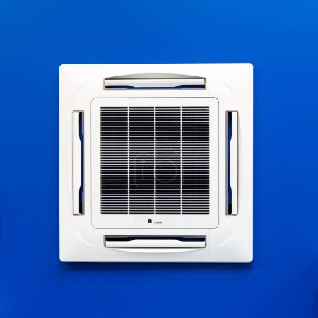 Ceiling air conditioner, split system installed on blue background. Ventilation and conditioning technology