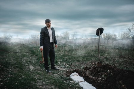 Maniac with an axe against grave with victim wrapped in a canvas, serial murderer concept, night crime horror, violence