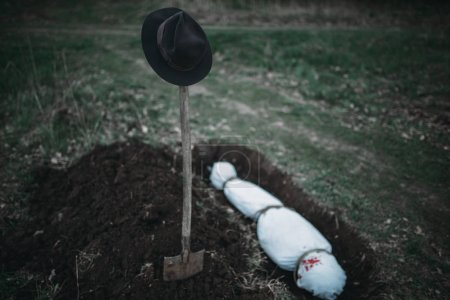 Grave with maniac victim wrapped in a canvas, serial murderer concept, night crime horror, violence