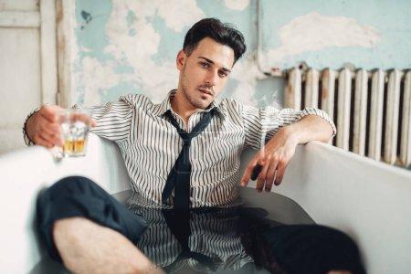 Drunk businessman bankrupt in bathtub, suicide man concept. Problem in business, stress