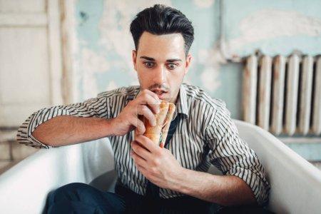 Anxious businessman bankrupt eats burger in bathtub before his death, suicide man concept. Problem in business, depression