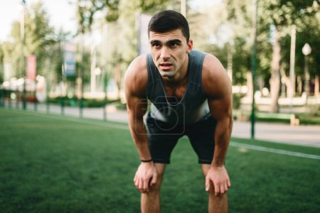 Muscular male athlete prepares for the training, fitness workout. Strong sportsman in park